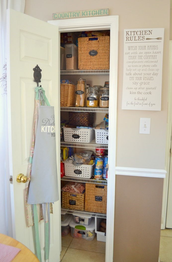 organized pantry with thrifted baskets and jars and chalkboard labels
