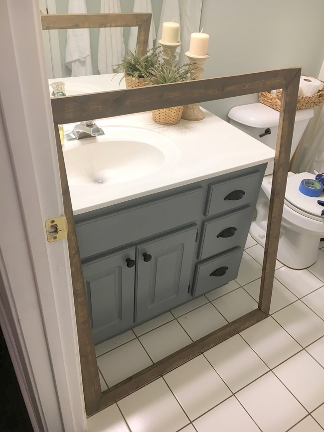 Stained wood framed bathroom mirror