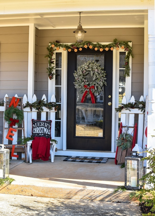 Farmhouse style Christmas front porch with picket fences-19
