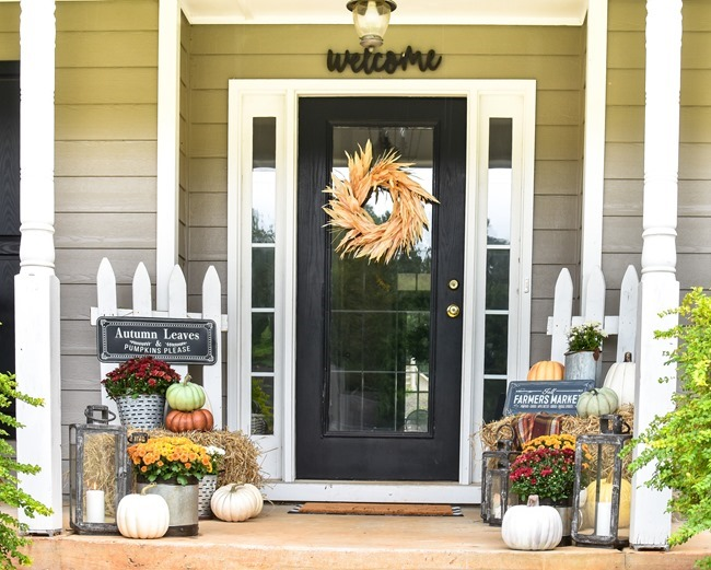 Farmhouse fall front porch with lots of mums, hay and pumpkins-21